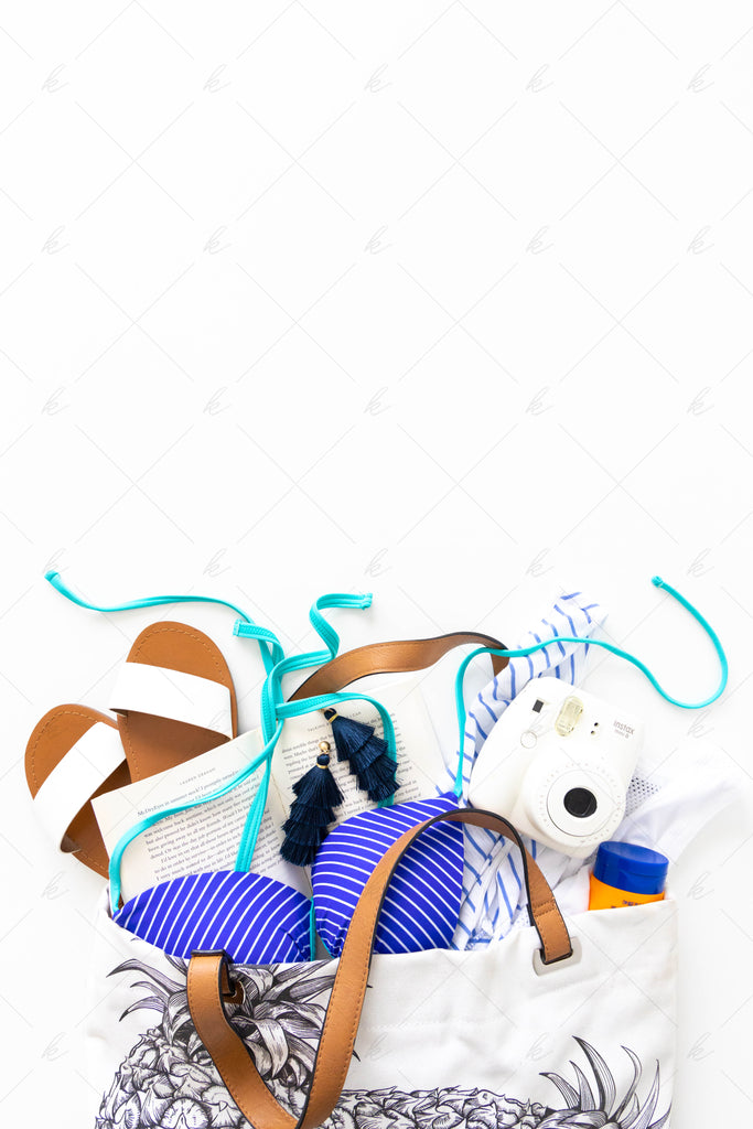 pineapple beach bag with sandals, sunscreen, camera, book, earrings, and bathing suit summer stock photo