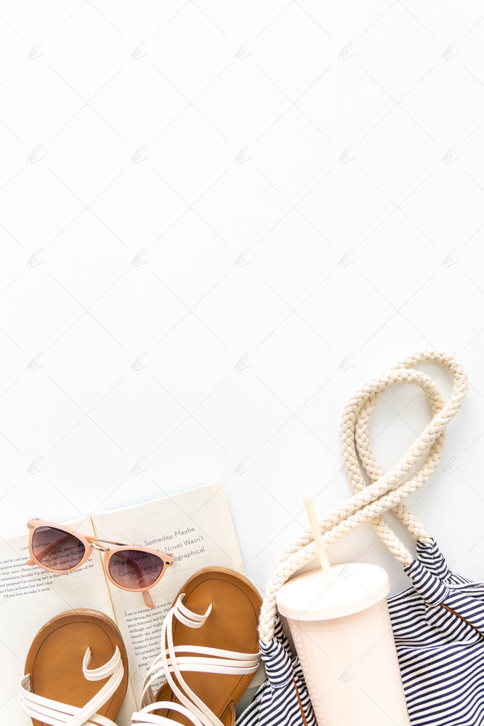 Beach bag with white sandals, sunglasses, book, and tumbler