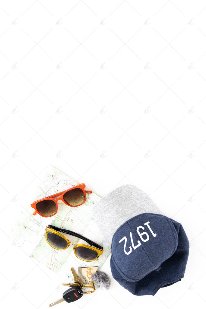 Blue hat with red and yellow sunglasses, keys, and a map stock photo image