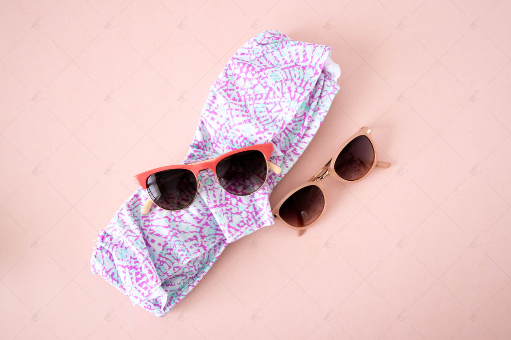 pink and blush sunglasses, pink and teal bathing suit on a pink background summer stock photo
