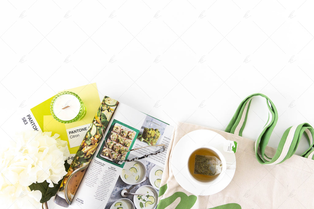 green bag with tea, green magazine, green candle, fresh flowers, and pantone color cards stock photo