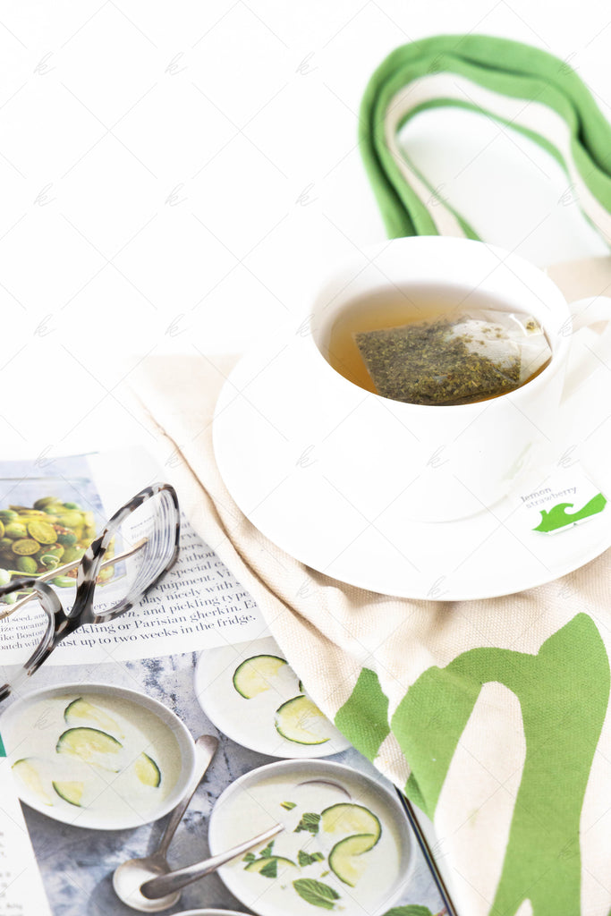 green bag with tea, green magazine, and glasses stock photo