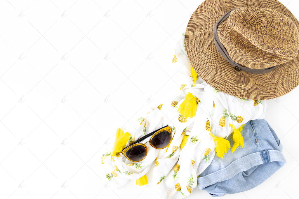 yellow sunglasses with hat, jean shorts, and a yellow pineapple top summer stock photo