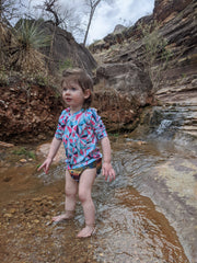 Infant standing in water outdoors.