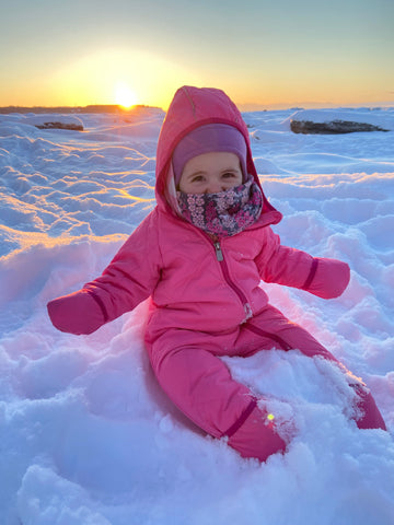 Baby playing in the snow at sunset