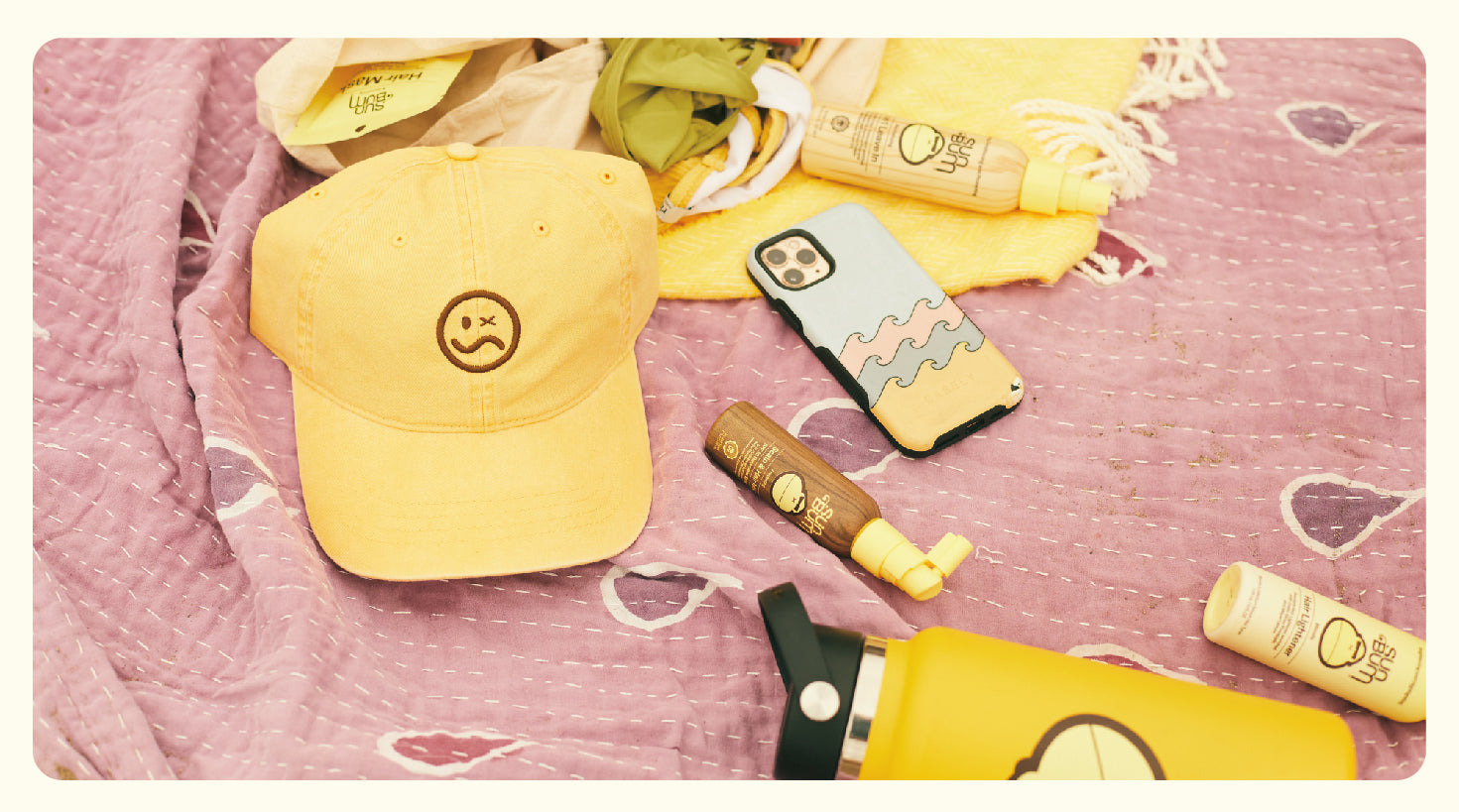 The Summer McKeen x Sun Bum Dad Hat on a towel with Sun Bum hair products