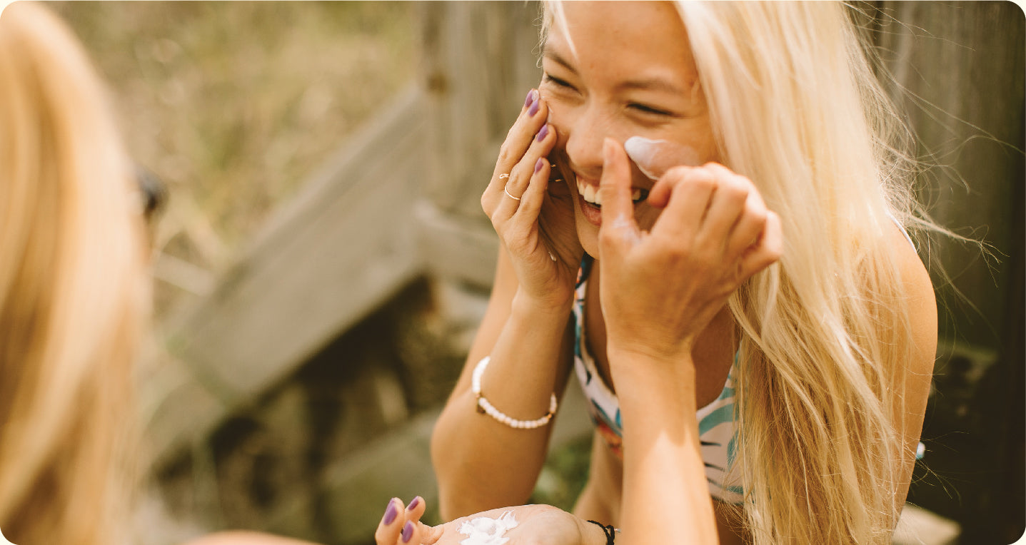 Girl applying sunscreen to her face on the beach