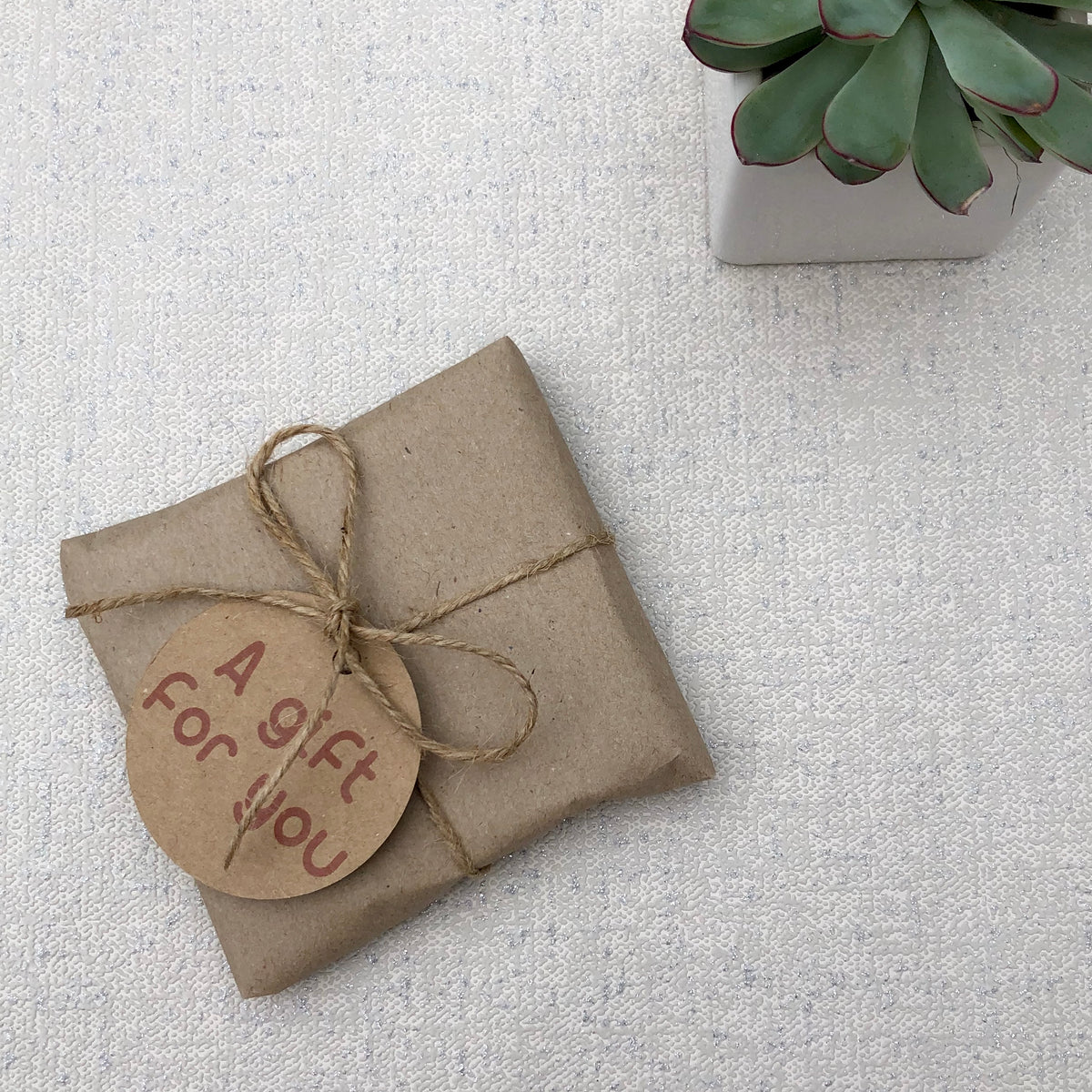 Wood slice photo gift wrapped in rustic brown paper and string.