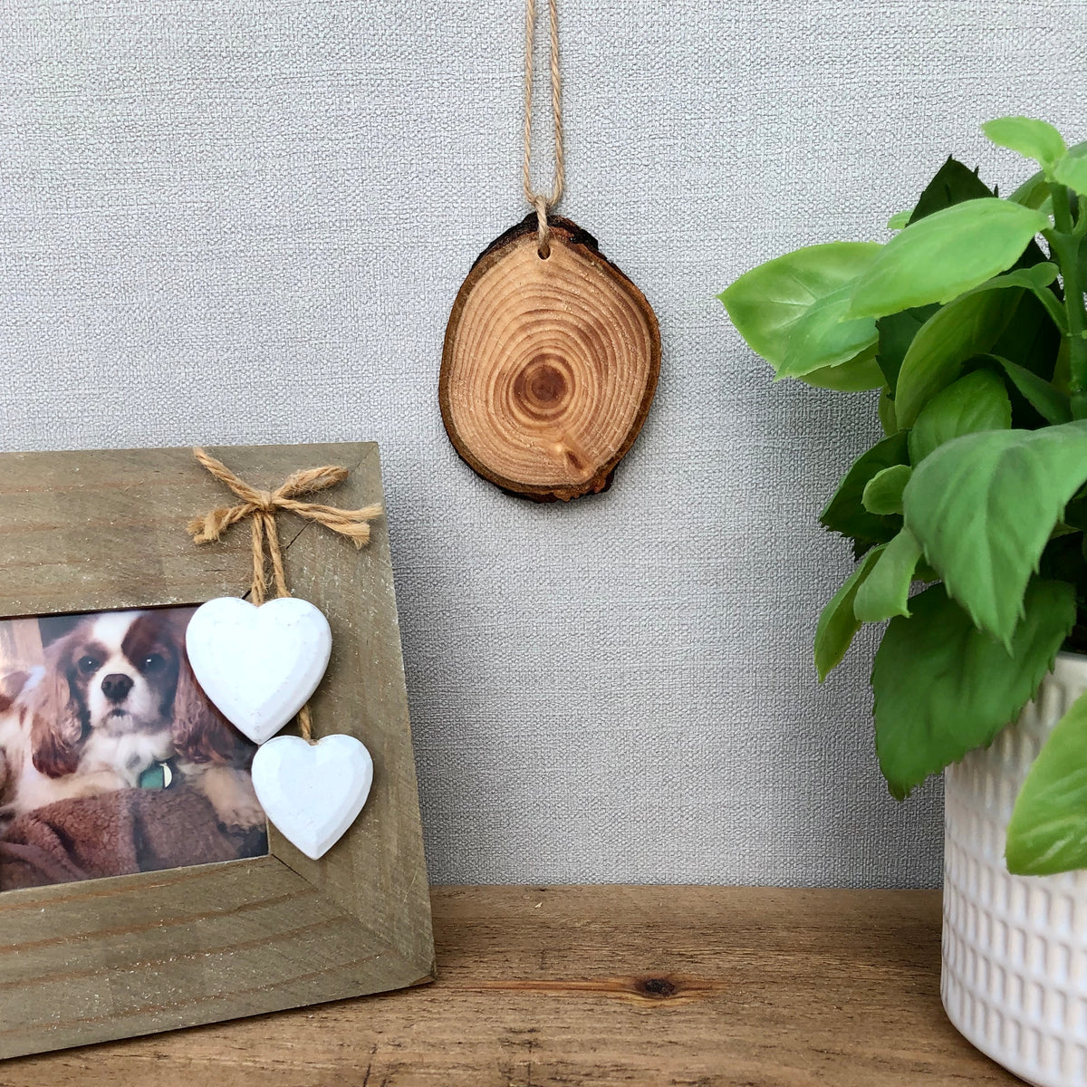 A wood slice air freshener displayed near a photo frame and a plant
