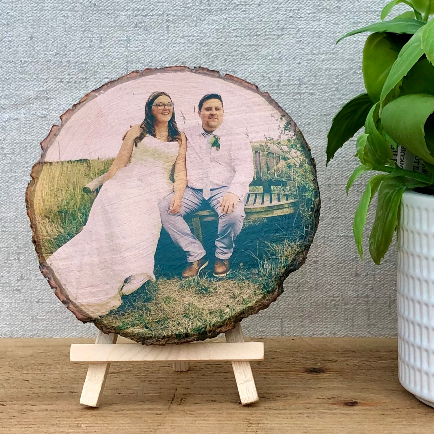 A wood slice photo plaque showing a bride and groom on their wedding day