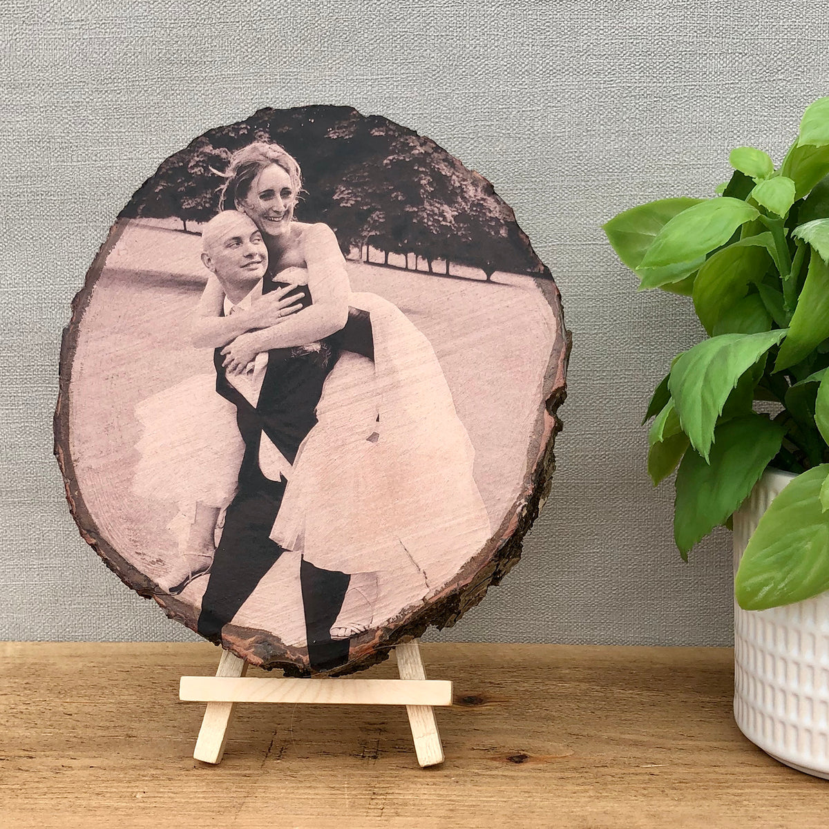 A large wood slice photo plaque showing a bride and groom on their wedding day
