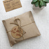 A wood slice photo plaque, gift wrapped in rustic brown paper, twine and a swing tag saying a gift for you.