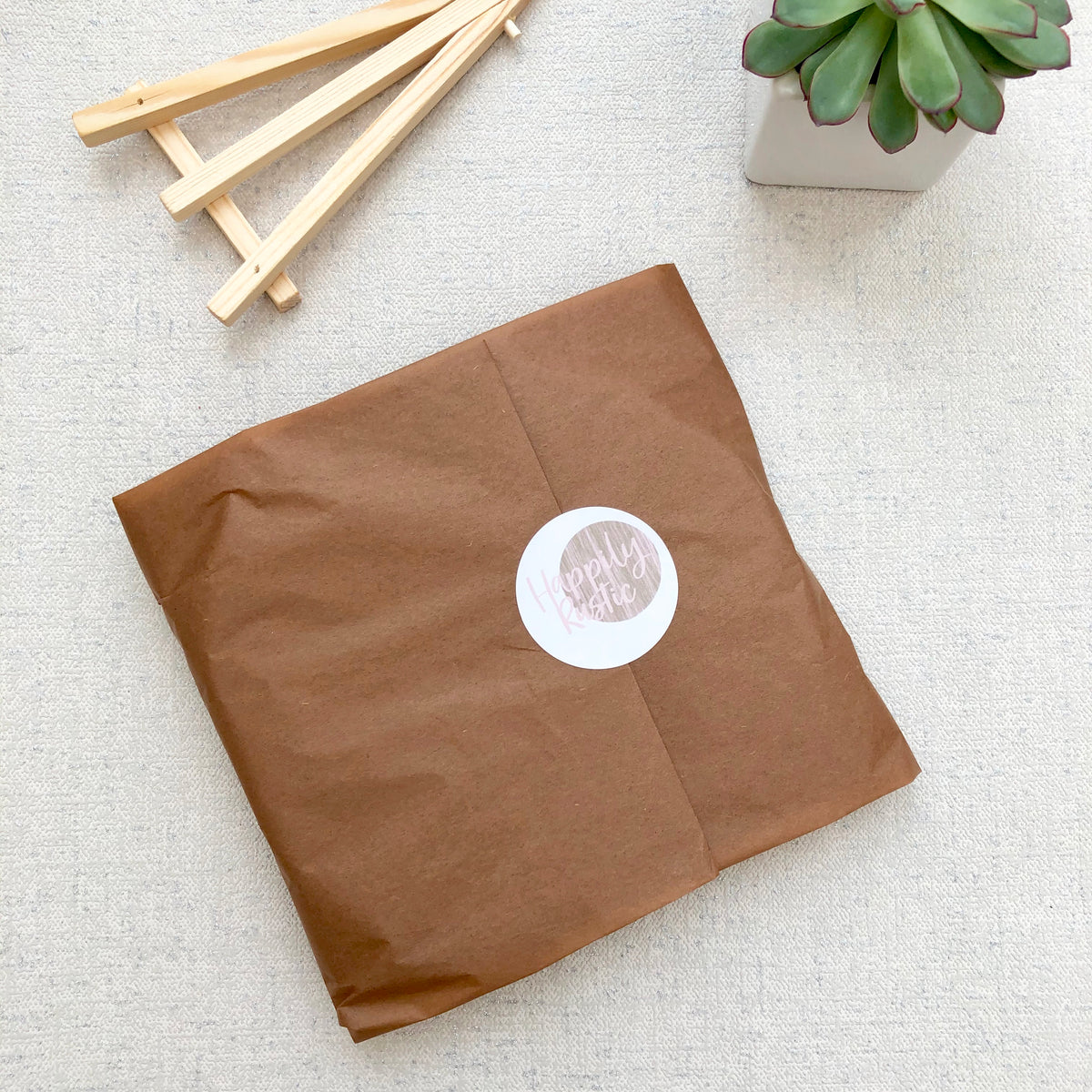 A wood slice photo gift wrapped in brown tissue paper with a Happily Rustic sticker. A wooden stand and small plant are also shown.