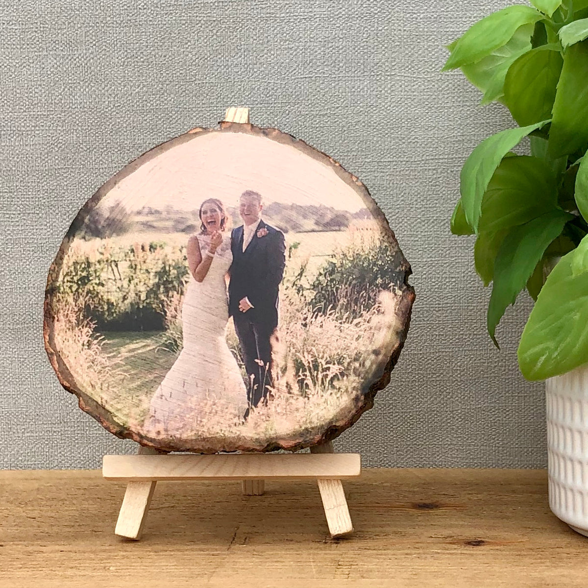 A small wood slice photo plaque showing a bride and groom on their wedding day