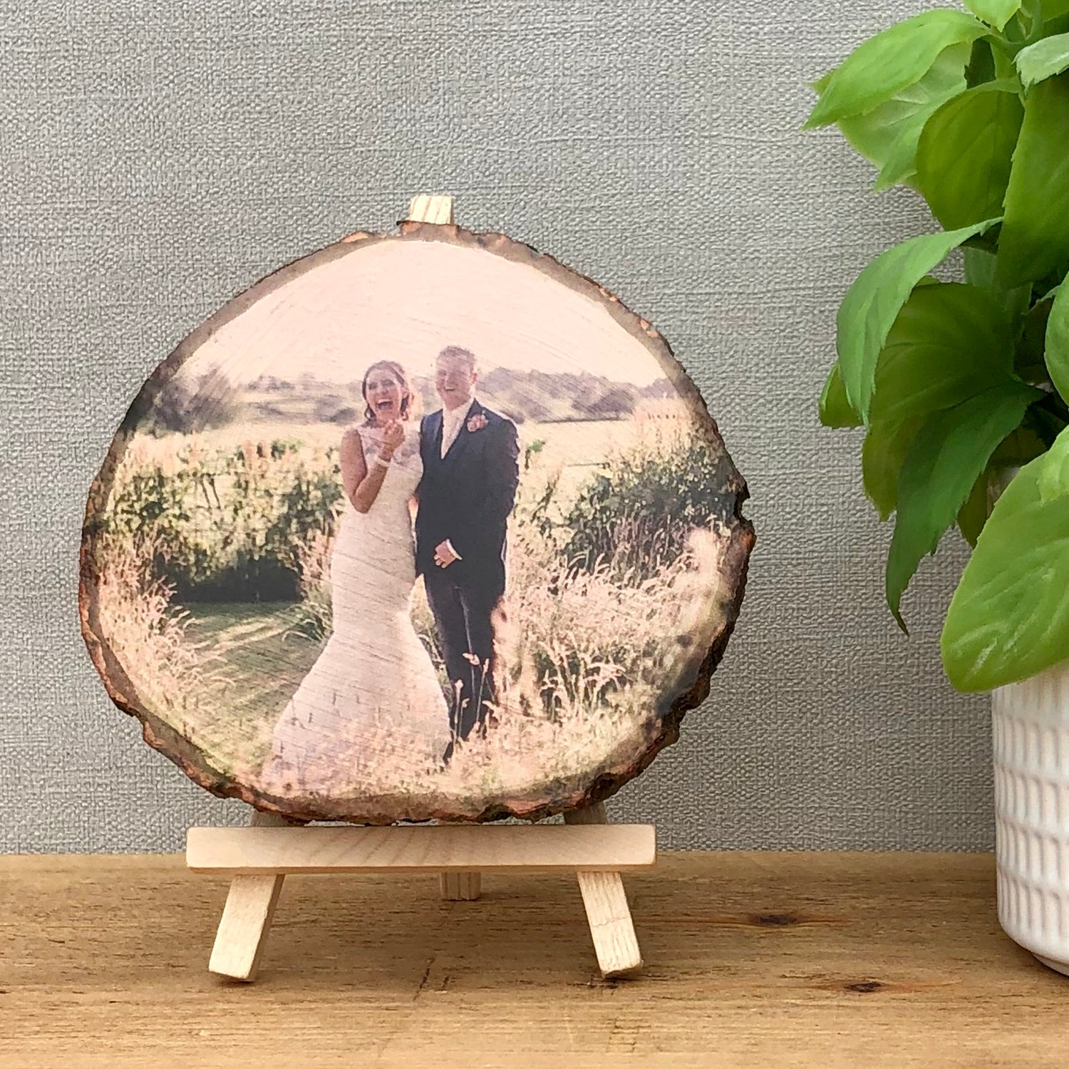 A wood slice photo plaque showing a bride and groom on their wedding day.
