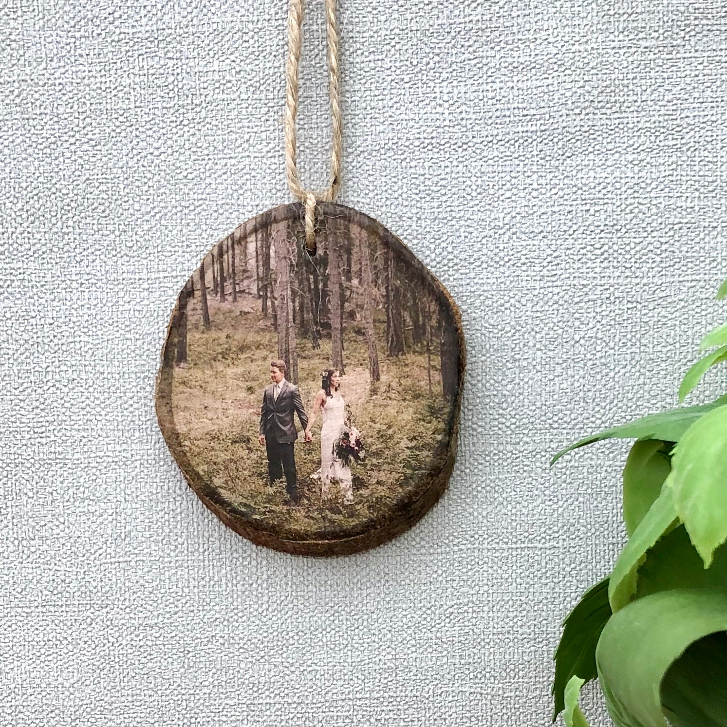 a wood slice hanging photo ornament showing a bride and groom on their wedding day.