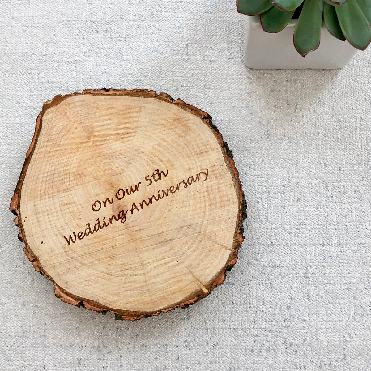 "A wood slice with the words ""on our 5th wedding anniversary"" engraved on it."