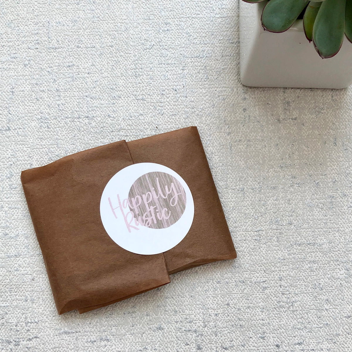 A wood slice photo gift wrapped in brown tissue paper with a Happily Rustic sticker.