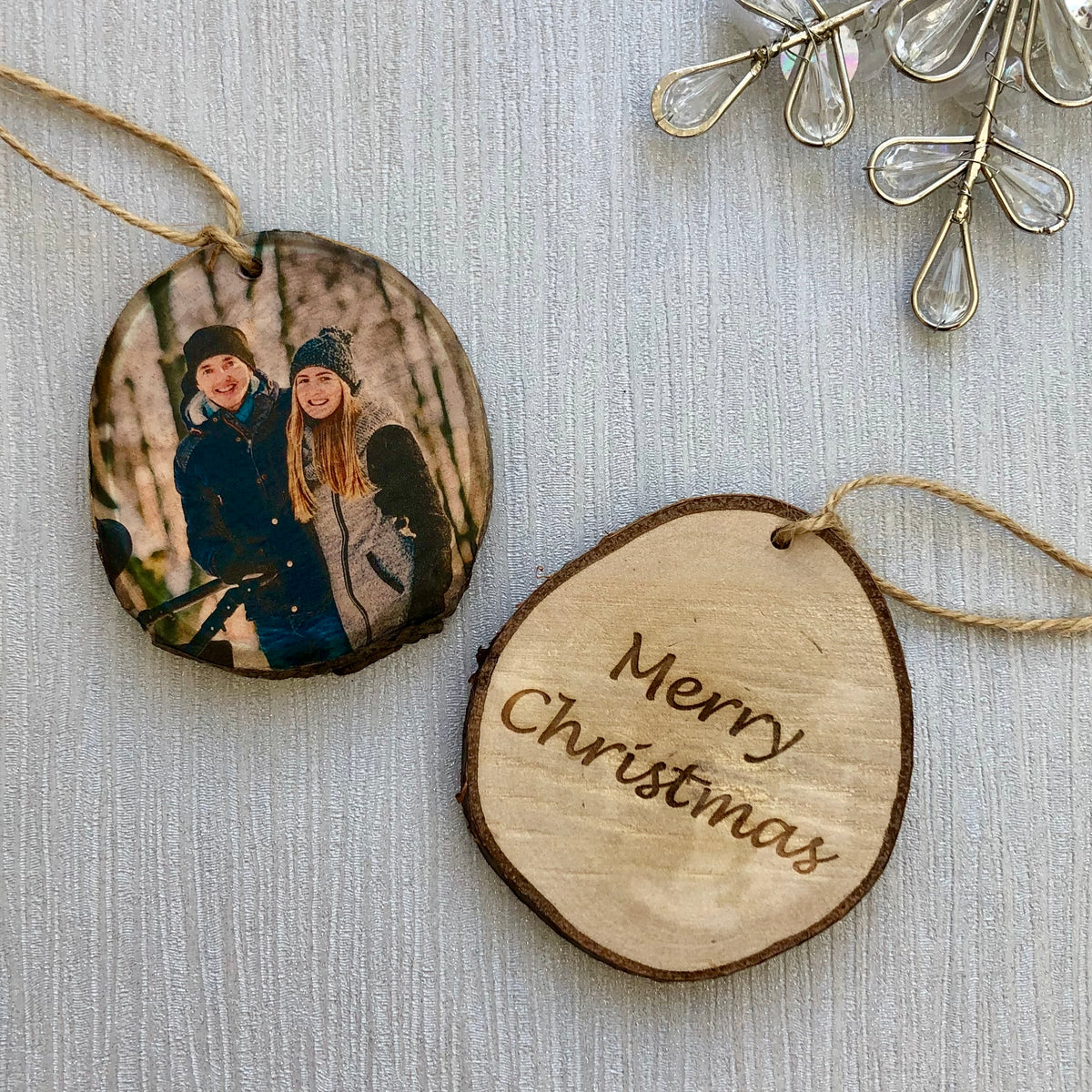 Two wood slice christmas tree decorations, one has a photo of a couple, the other has the words Merry Christmas engraved.