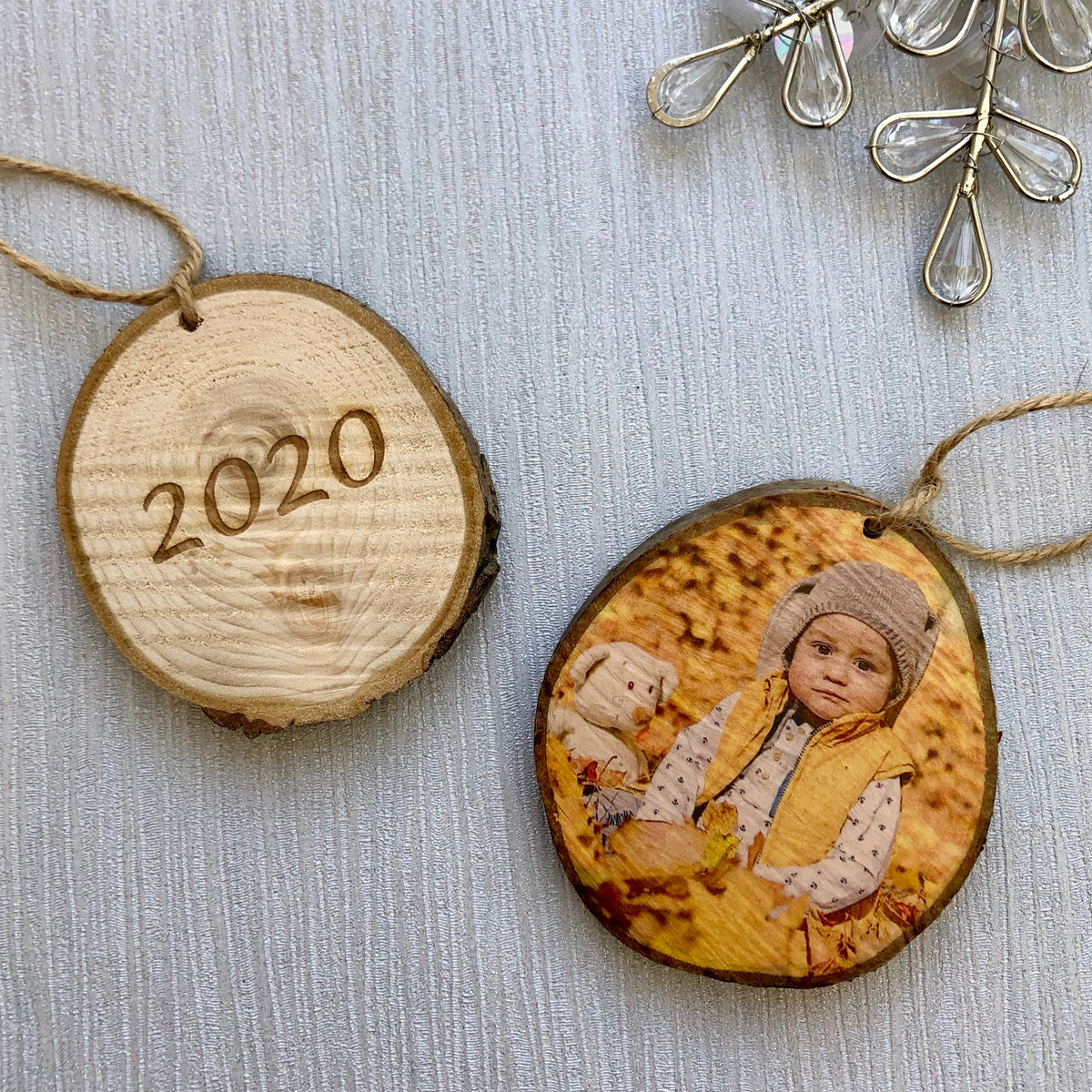 Two wood slice christmas tree decorations, one has a photo of a baby, the other has the 2020 engraved.