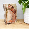 A half log freestanding wooden plaque showing a bride and groom on their wedding day.