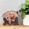 A house shaped wood slice plaque showing a mum, dad and baby.