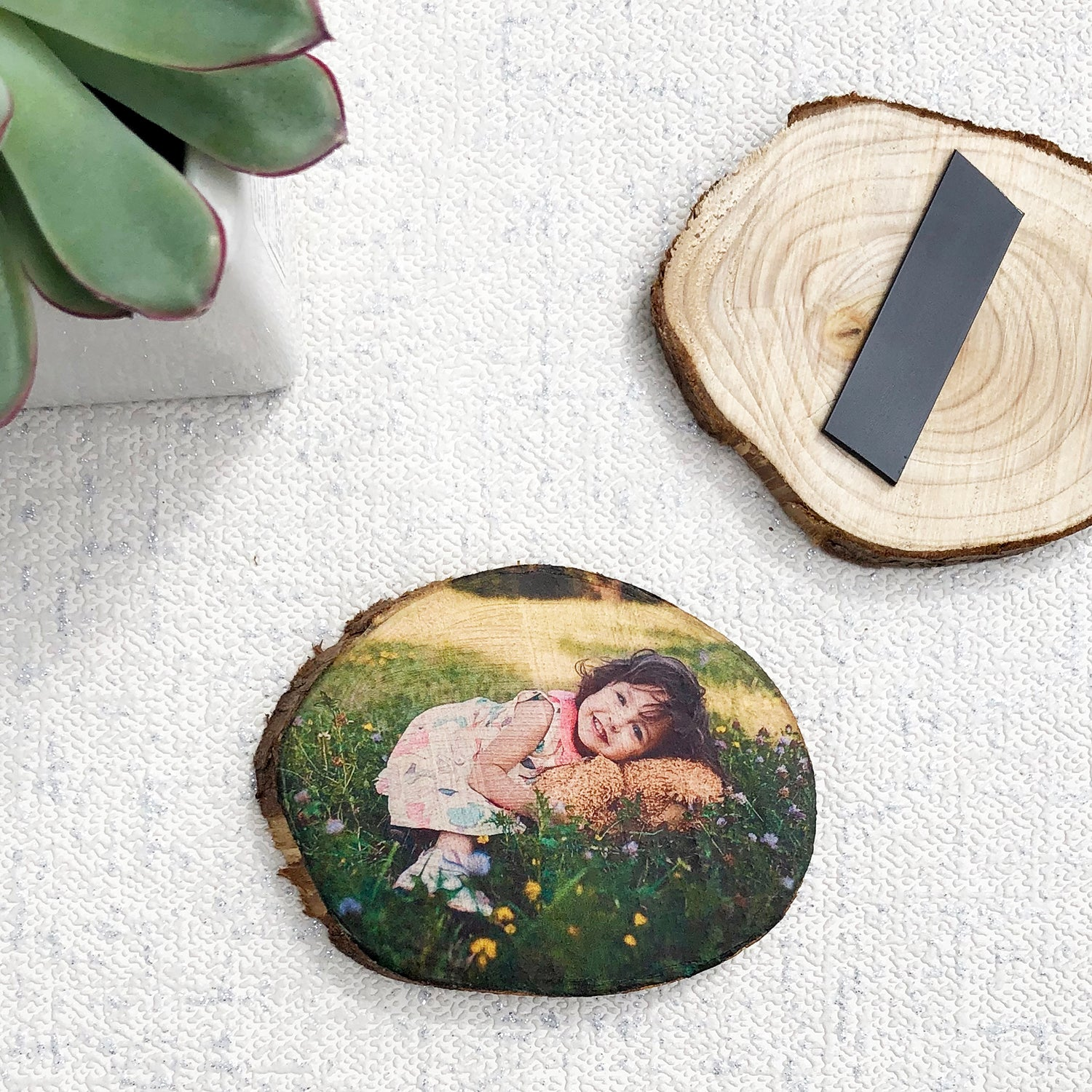 A wood slice fridge magnet showing a small child lying in a meadow. Photo also shows the back of a fridge magnet and a small plant.