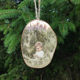 Wood slice christmas tree decoration, hanging with twine. Showing a small boy sat in a grass meadow.