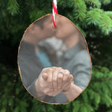 Wood slice hanging christmas tree decoration showing a couple holding hands, their hands are nearest to the front showing an engagement ring