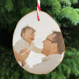 Wood slice hanging christmas tree decoration showing a man holding a smiling baby up