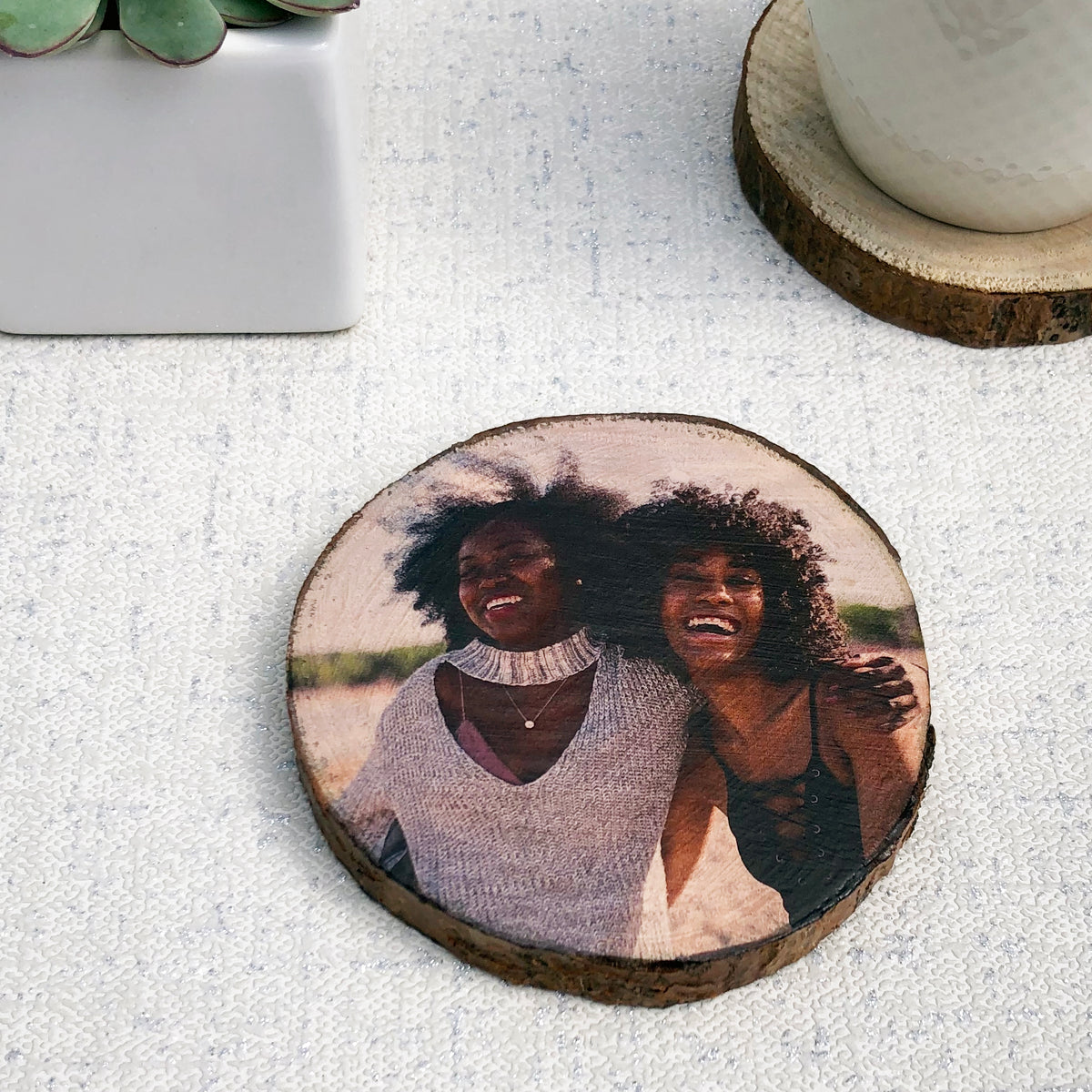 A wood slice photo coaster showing two friends laughing. A cup of tea on a plain coaster and a plant are also shown.