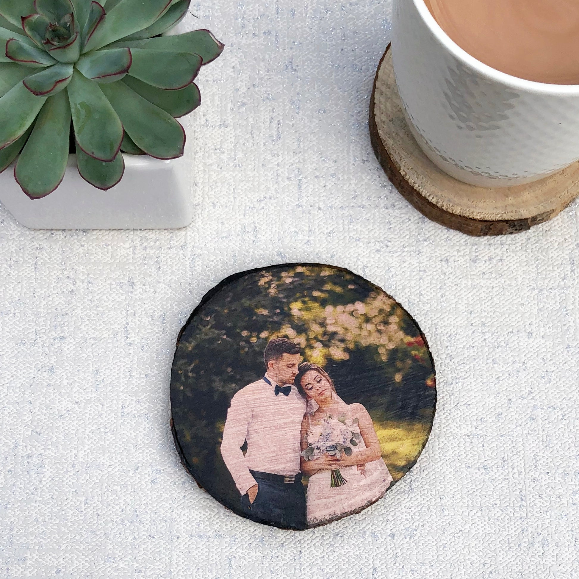 A wood slice photo coaster showing a bride and groom on their wedding day. A cup of tea on a plain coaster and a plant are also shown.