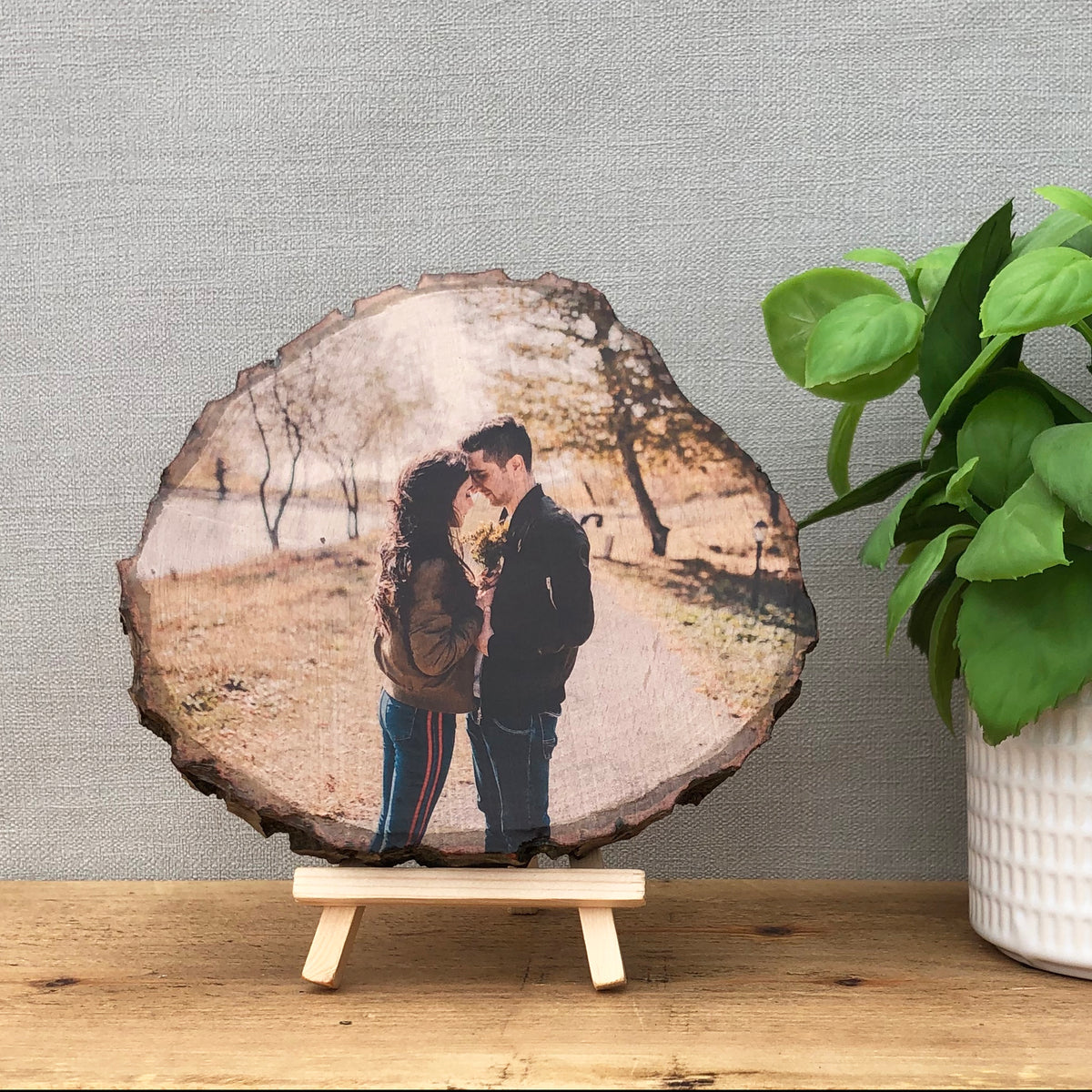 A wood slice photo plaque showing a couple looking at each other, they are outside in a woodland area.