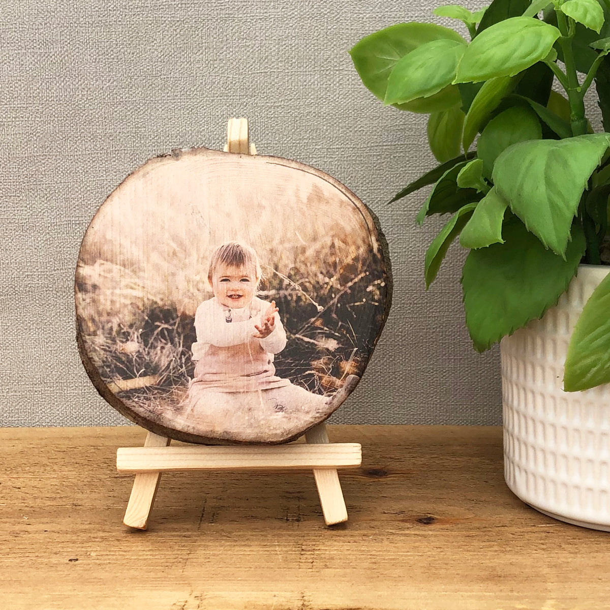 A wood slice photo plaque showing a young child sat in a meadow.