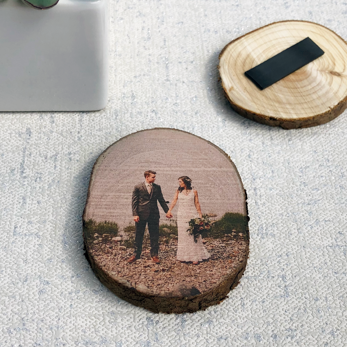 A wood slice fridge magnet showing a bride and groom on their wedding day.