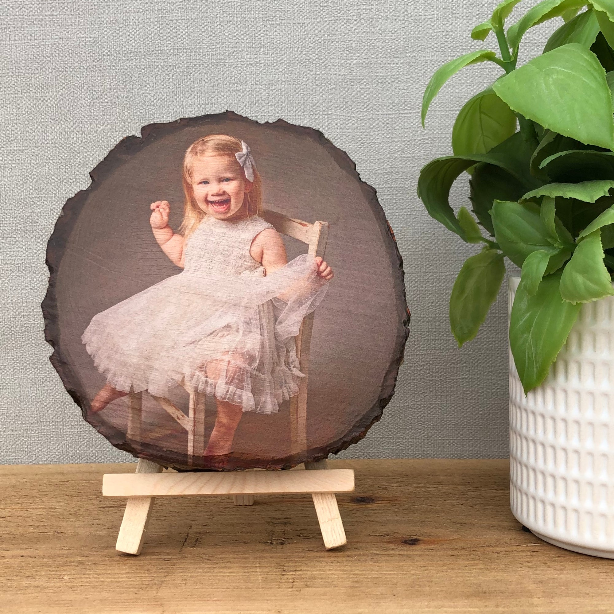 A wood slice photo plaque showing a young child sat on a chair.