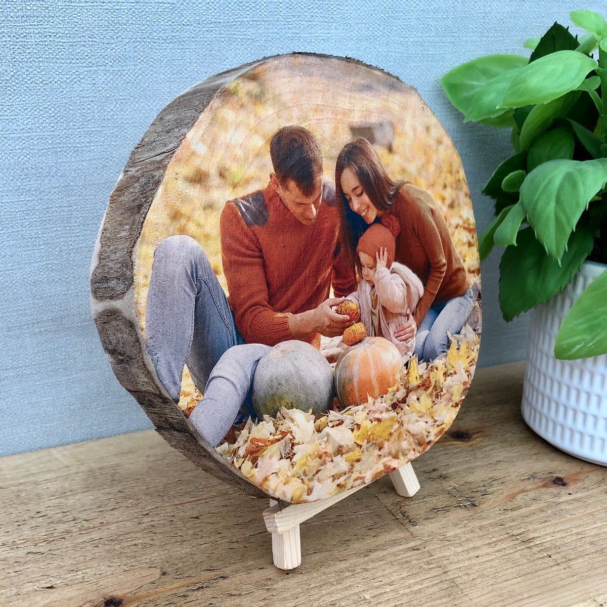 A wood slice photo plaque showing a family sat on grass surrounded by pumpkins. The wood slice has no bark (live edge)