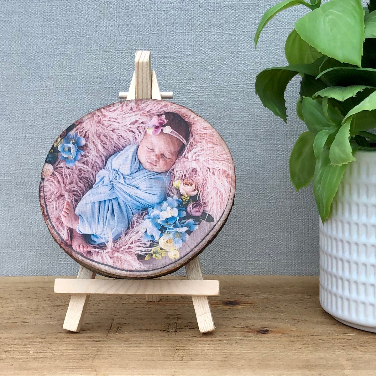 A wood slice photo plaque showing a newborn baby wrapped in a blanket, lying on feathery cushions.