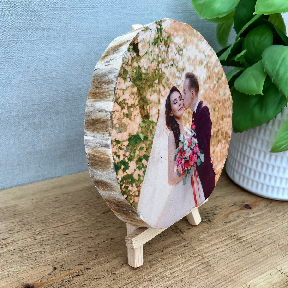 a wood slice photo plaque showing a bride and groom on their wedding day. the wood slice has no bark (live edge)