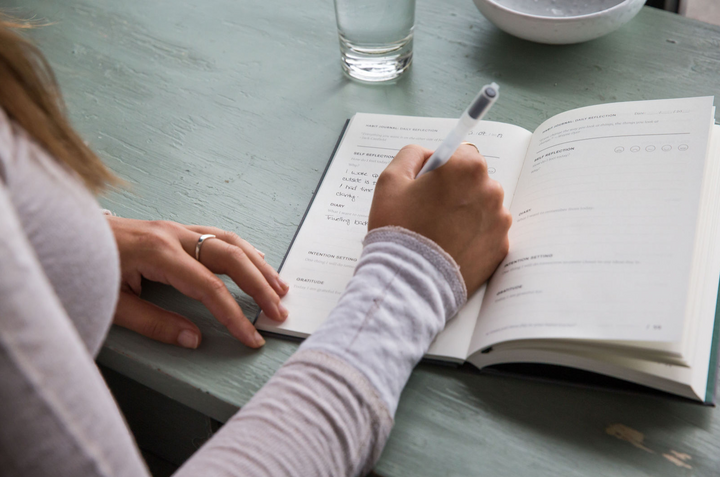 Young Woman Writing in Habit Journal on Breakfast Table