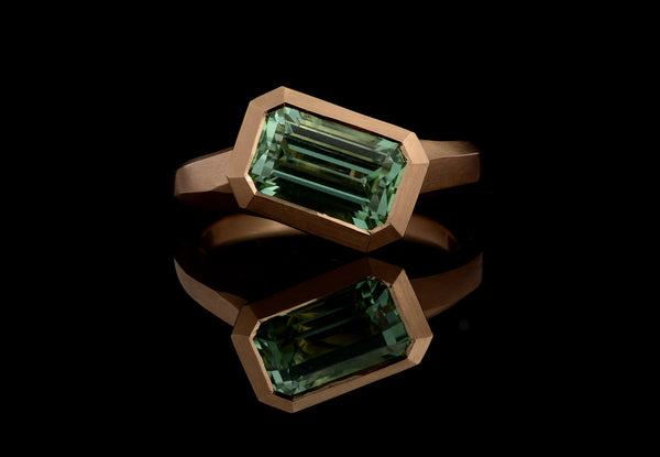 Carved rose gold arris ring with emerald cut mint green tourmaline