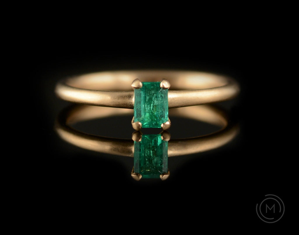 Bright green emerald and rose gold four claw engagement ring