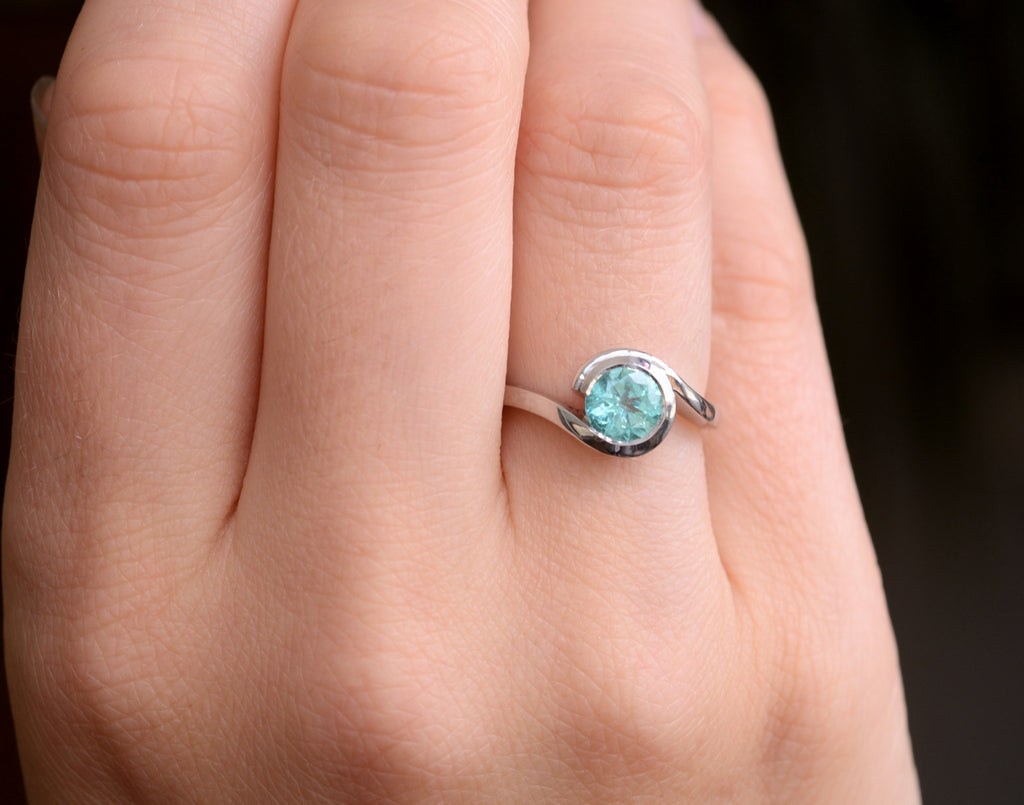 Bespoke platinum and paraiba tourmaline engagement ring on hand