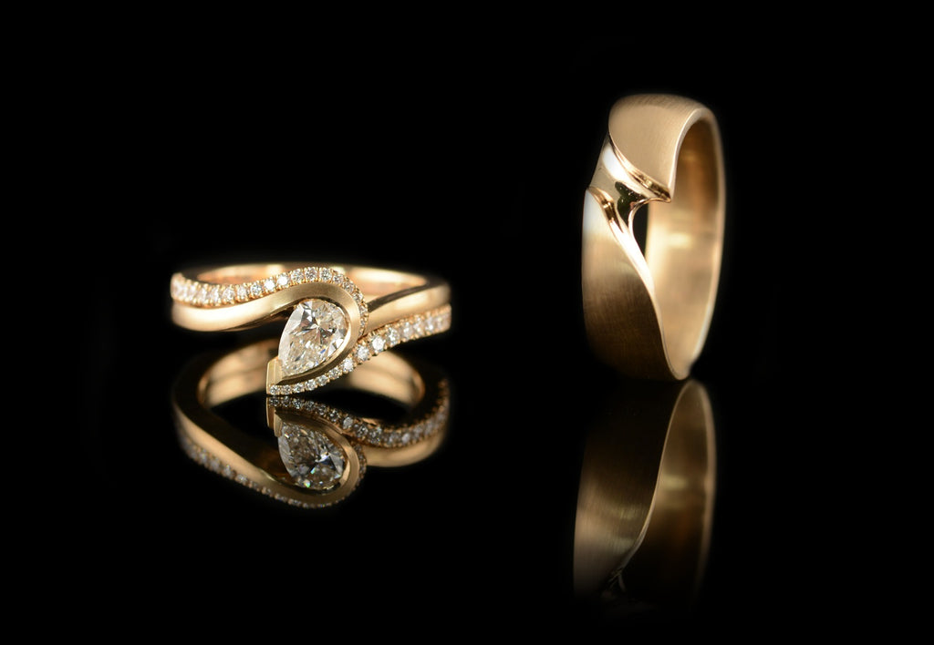 pear shaped wave engagement ring with carved mens band