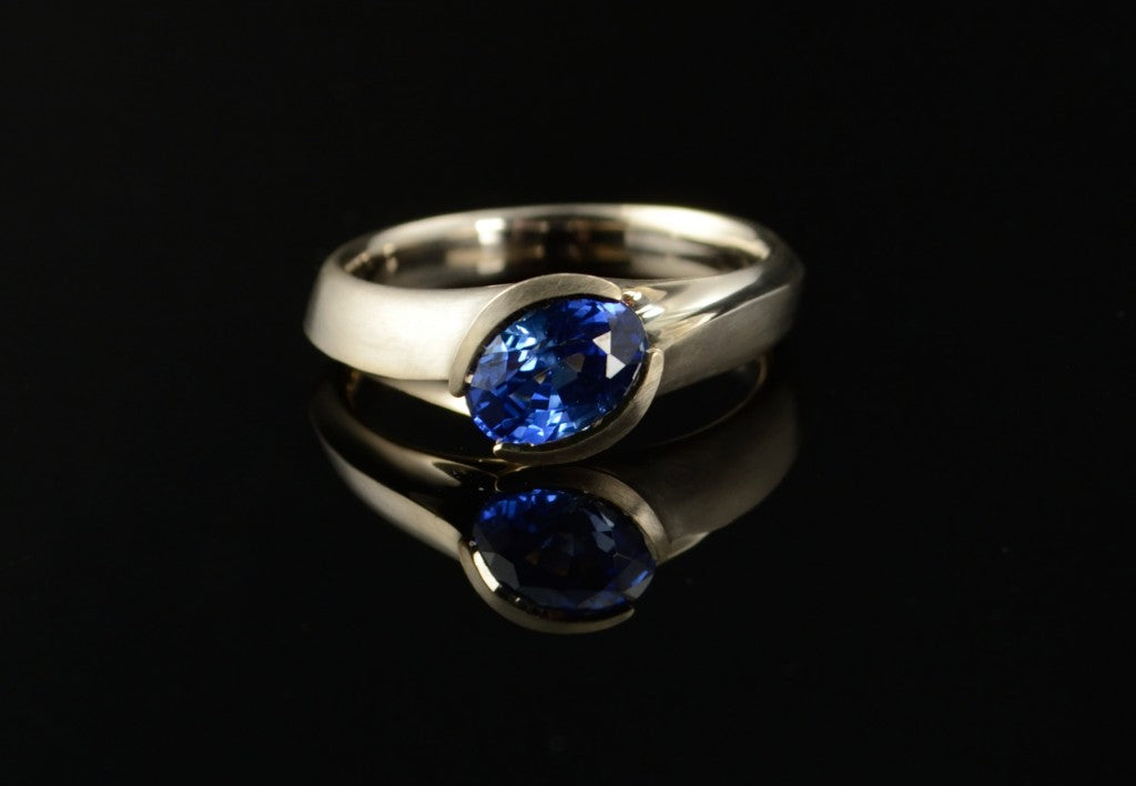 Carved white gold and blue coloured sapphire engagement ring