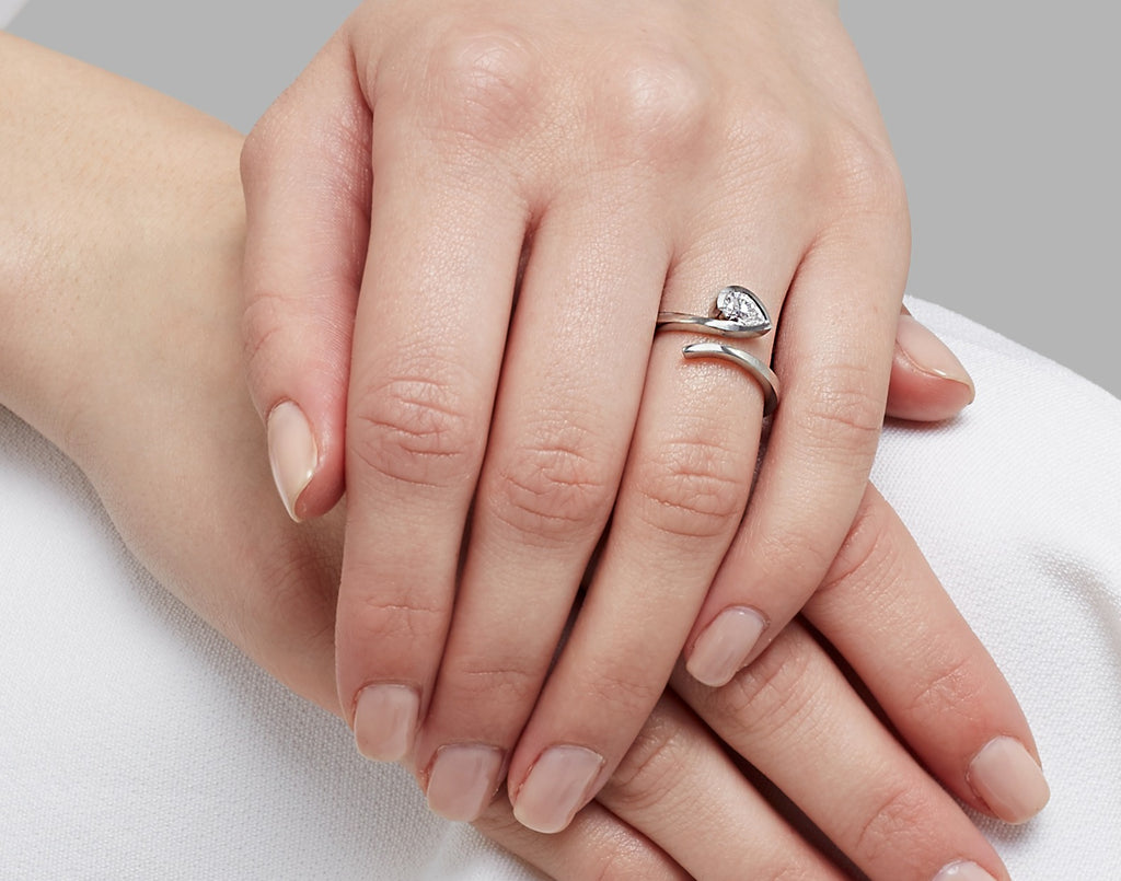 Platinum and pear white diamond solitaire engagement ring on hand