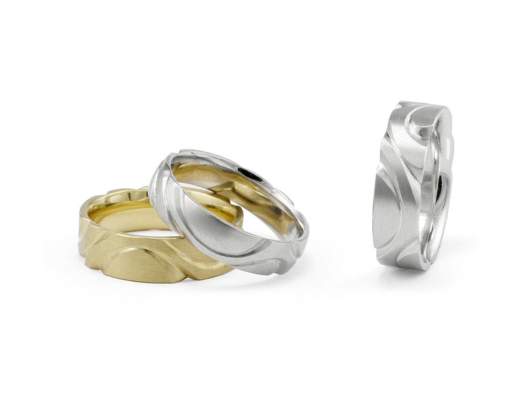 Hand-carved men's wedding rings in gold and platinum