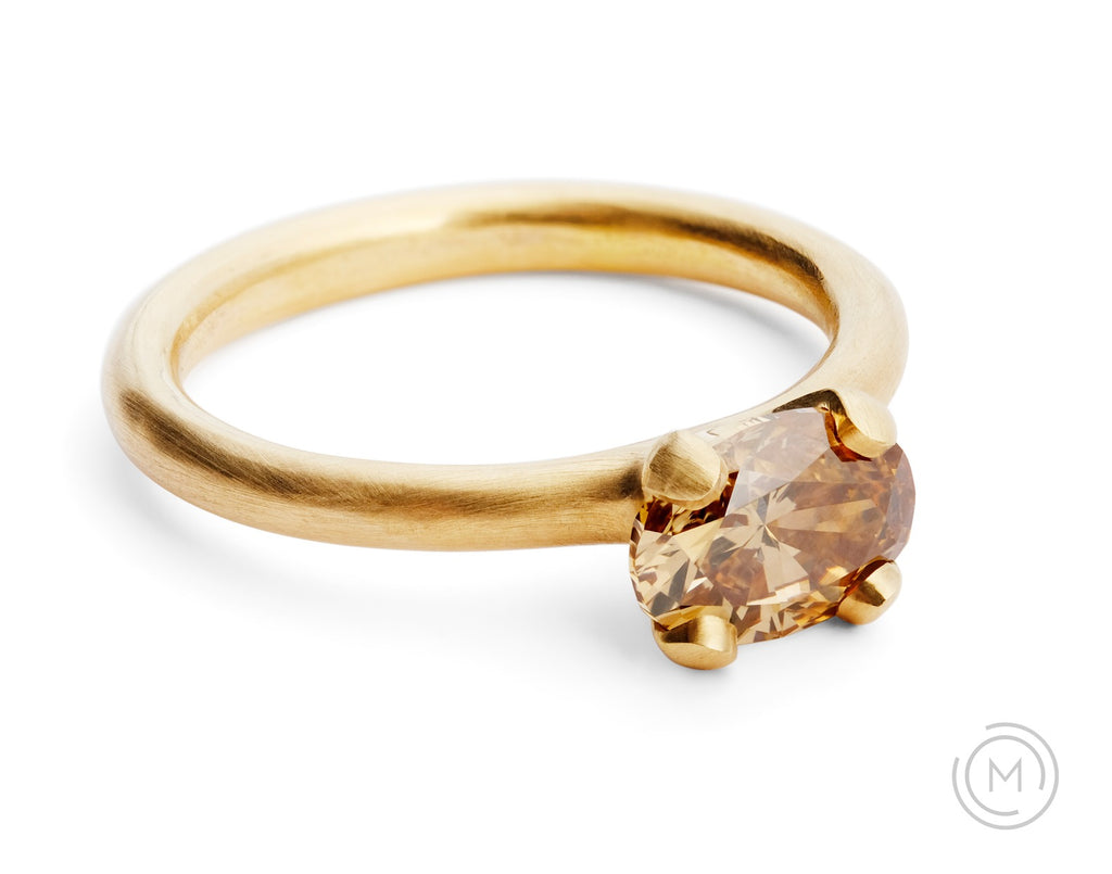 Modern rose gold solitaire engagement ring with oval cognac diamond