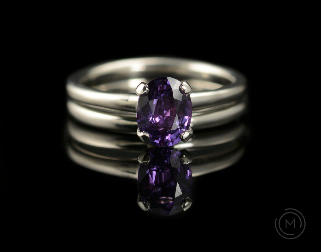 Four claw engagement ring with oval purple coloured sapphire gemstone