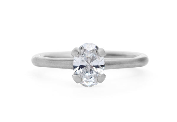 Oval white diamond and platinum sculpted four claw solitaire engagement ring